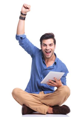 hombre sentado: hombre sentado celebrando el �xito, mientras trabaja en la computadora pad tablet
