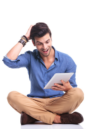 amazed young seated casual man reading good news on his tablet pad computer while seated on white background photo