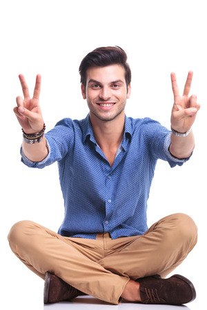 rest in peace: seated casual man making the victory sign and smiles on white background