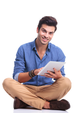 smiling seated casual man working on his tablet pad computer, on white background photo