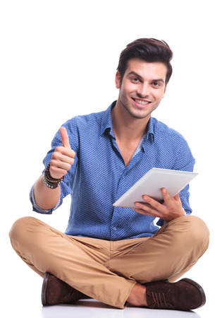 positive seated casual man with tablet pad computer making the ok thumbs up hand sign photo
