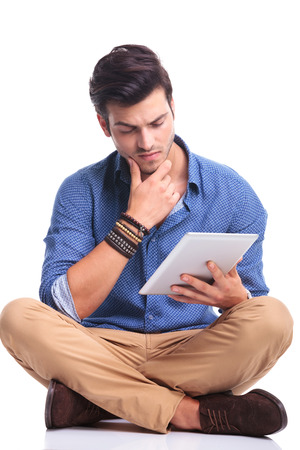 worried young casual man reading on a tablet pad computer, thinking  photo