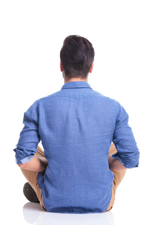back veiw of a seated young brunette man , on white background photo