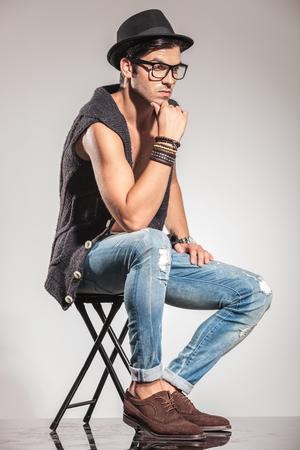 hombre sentado: vista lateral de un hombre joven pensativo sentado mirando a la cámara del te Foto de archivo