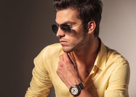 side view of cool fashion mans face, wearing glasses and looks away while thinking at something photo