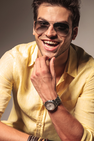 portrait of a seated laughing fashion man wearing sunglasses on gray studio background photo