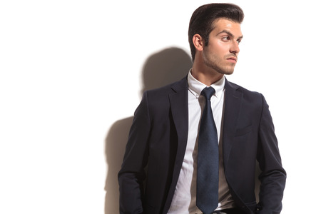 young fashion business man looking over his shoulder to his side, on white background photo