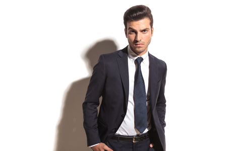 serious young elegant business man standng in studio on white background photo
