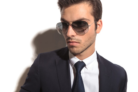 closeup picture of a young business mans face, wearing sunglasses and looking away to a side photo