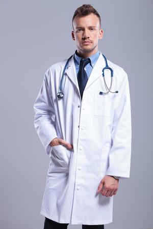 doctoring: grave giovane medico su sfondo grigio studio Archivio Fotografico