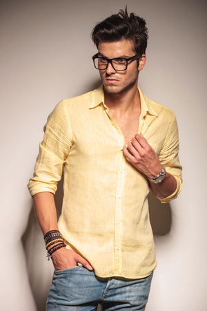side view of a casual fashion man model looking away to his side while pulling his collar