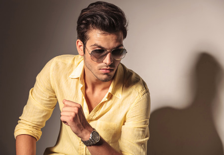 young style: attractive sexy man wearing sunglasses and yellow shirt, looks awy from the camera
