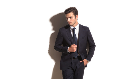 side view of an elegant business man looking away while leaning against white wall photo