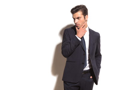 elegant business man thinking and looks away to his side on white studio background photo