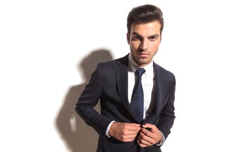 dramatic fashion business man unbottoning his coat on white studio background photo