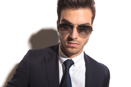 handsome business mans face wearing sunglasses in a closeup portrait on white background photo