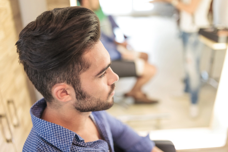 men shirt: side view of a seated young casual man with nice hairstyle, waiting Stock Photo