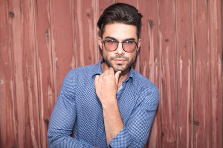 male facial: young casual man with glasses thinking and looks at the camera against wooden wall