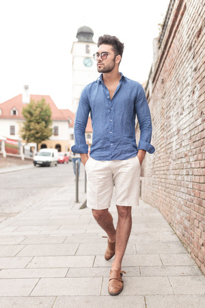 young casual man walking and looks to side in the city Stock Photo