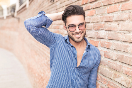彼の髪、れんが造りの壁の近くの屋外の写真を修正する彼の頭に手で笑みを浮かべてカジュアルな男 写真素材 - 31160301