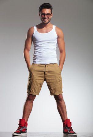 undershirt: full body picture of a young casual man in undershirt and shorts smiling with hands in his pockets