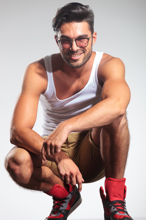 crouched: happy crouched casual man smiling to the camera in studio Stock Photo