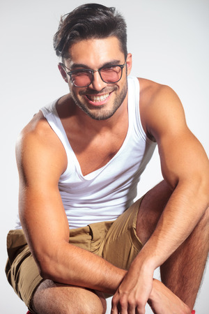 undershirt: smiling face of a man standing crouched in studio