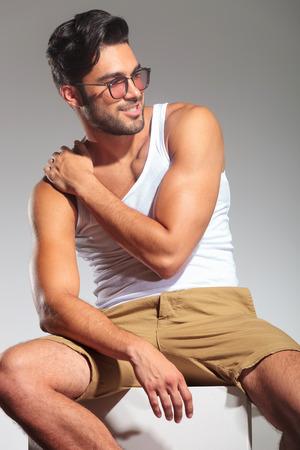 hombre sentado: vista lateral de un hombre sentado sexy con la mano en el hombro mirando a otro lado a su lado