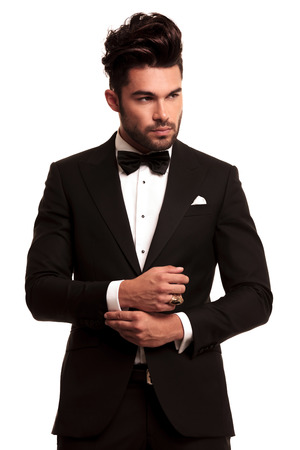 fashion elegant man in tuxedo fixing his sleeve on white background Stock Photo