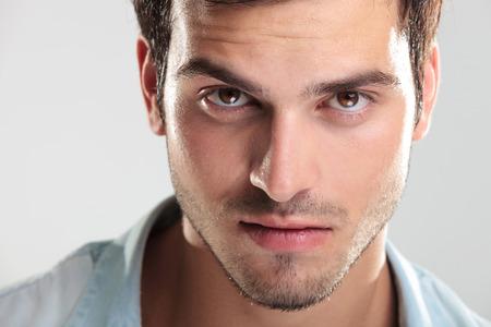 Close-up van een knappe man in blauw shirt, kijkend naar de camera