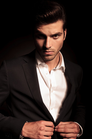 portrait of a young fashion man buttoning his suit on black studio background Stock Photo