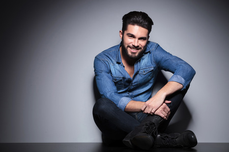 Handsome man in blue shirt smilling and sitting photo