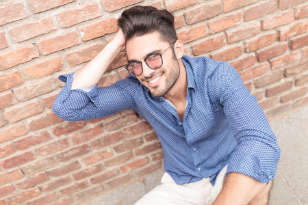 young casual man with glasses fixing his hair while seated against brick wall photo