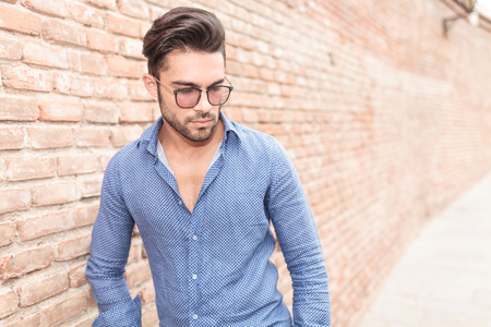 men shirt: young casual man with glasses looks down while standing near brick wall Stock Photo