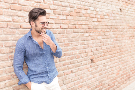 near side: side view of a smiling casual man near brick wall wondering about something
