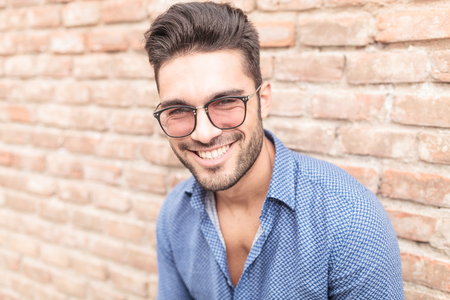 closeup picture of a happy smiling young casual man with glasses leaning against brick wall  photo