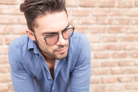 near side: closeup picture of a young casual man with glasses looking to his side ,  near brick wall