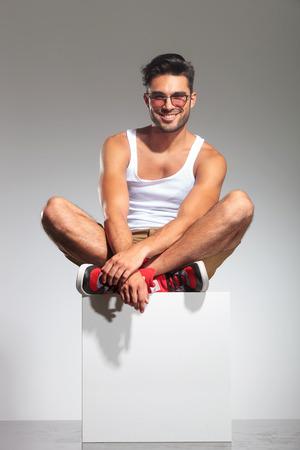 hombre sentado: hombre sentado en un cubo y sonrisas, es estudio con copyspace debajo de él Foto de archivo