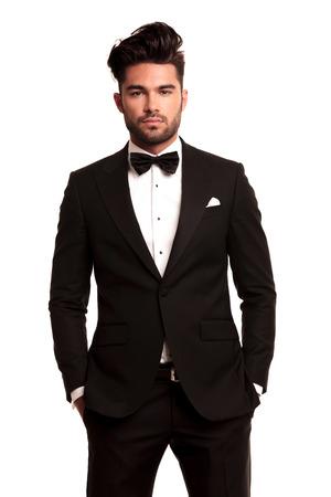 стильный мужчина в элегантном черном костюме и бабочкой, стоя с руки в карманах на белом фоне