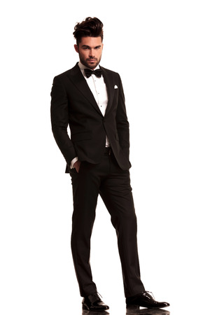relaxed elegant man in tuxedo looking at the camera on white background
