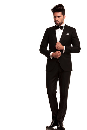 full length picture of an elegant young fashion man adjusting his tuxedo while looking to his side, away from the camera. on white background  photo