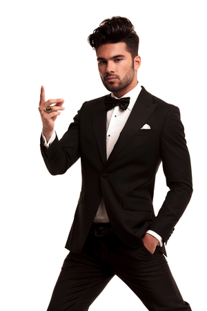 imposing fashion man in tuxedo snapping his fingers on white background photo