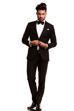 full body picture of an elegant man in tuxedo unbuttoning his coat on white background Foto de archivo