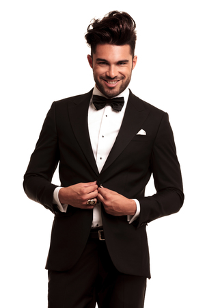 happy young elegant man in tuxedo buttoning his coat and smiles on white background