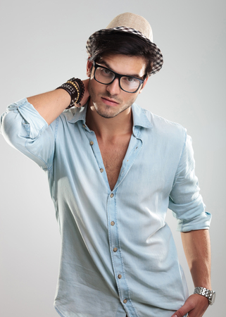 Studio photo of young attractive man wearing black glasses and hat Reklamní fotografie
