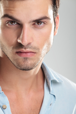 perfect face: Photo of a young casual man in blue shirt, looking at the camera