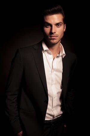 Jonge ontspannen zakenman met handen in zijn zakken op een donkere achtergrond