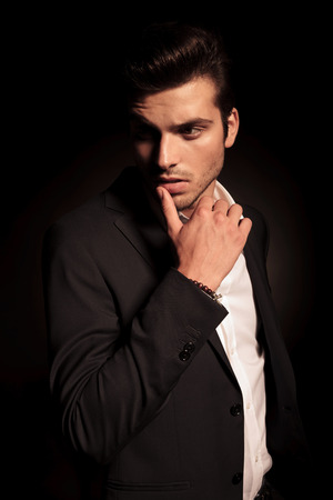 looking to side: side view of a fashion man in a provocative pose with finger on his lip , looking away from the camera