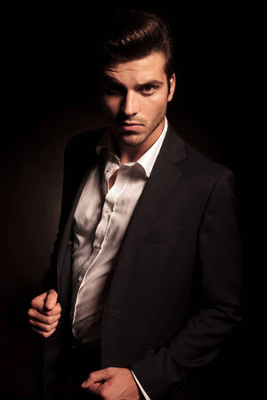 head collar: cool fashion man in suit pulling his coat in a fashion pose, in studio