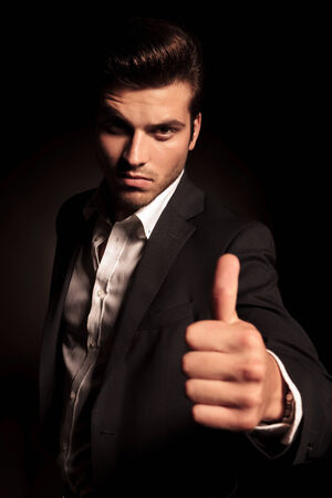 young elegant fashion man in suit making the ok thumbs up hand sign on black background photo